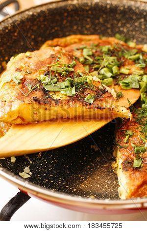 Stodgy Spanish Potato Tortilla With Herbs In Black Pan
