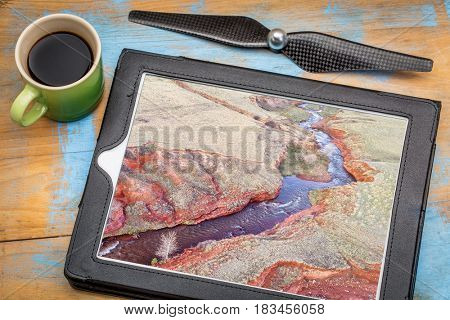 creek at Colorado foothills  - reviewing aerial pictures on a digital tablet with a cup of coffee