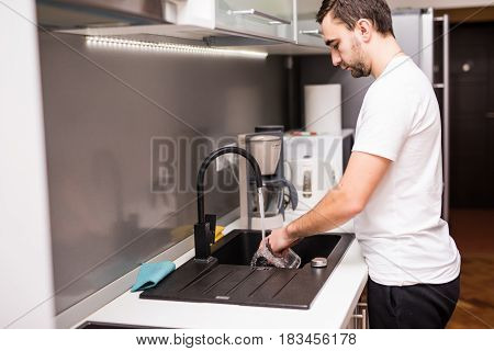 Happy Young Man Standing And Washing Dishes On The Kitchen