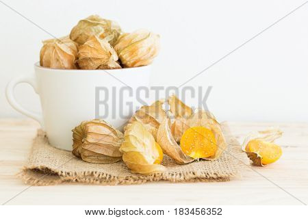 Cape gooseberry on sack on wooden table