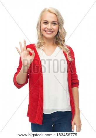 gesture, fashion, portrait and people concept - happy smiling young woman in red cardigan showing ok hand sign over white