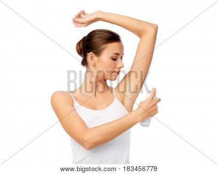 beauty, hygiene, bodycare and people concept - beautiful young woman applying antiperspirant or spray deodorant over white background