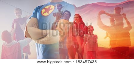 Concept of father's day! Man in superhero costume is protecting his family.