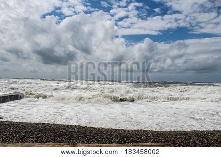 the raging sea during a storm, lit by the sun