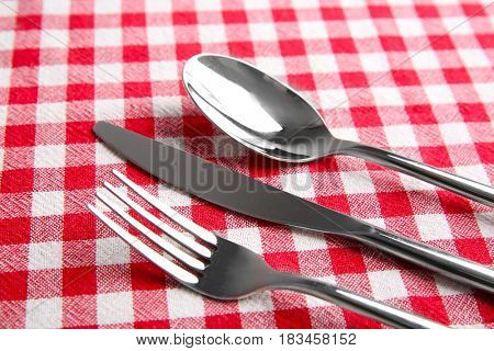 Table setting with silver cutlery on checkerboard napkin