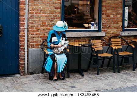 Bruges Belgium - July 29 2016: Old refined woman dressed in blue sitting on a terrace in the street of Bruges.