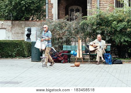 Bruges Belgium - July 29 2016: Musician playing guitar and harp in the streets of Bruges. The historic city centre is a World Heritage Site of UNESCO.