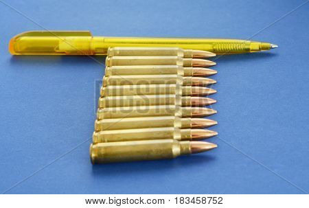 Cartridges 5.56mm Ammunition With Pen as a Concept of Propaganda in Mass Media. Fake News Invasion Concept.
