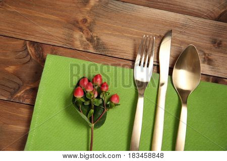 Table setting with golden cutlery and napkin on wooden background