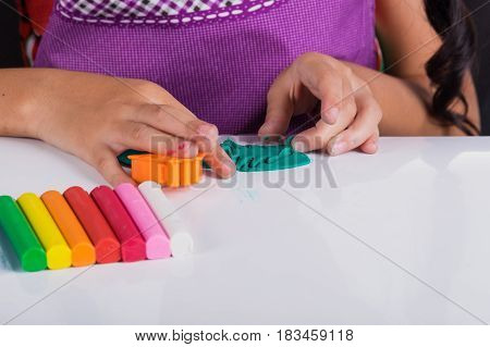 Little hand of kid learn to play colorful dough on white table