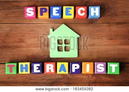 Colourful cubes with text SPEECH THERAPIST on wooden background