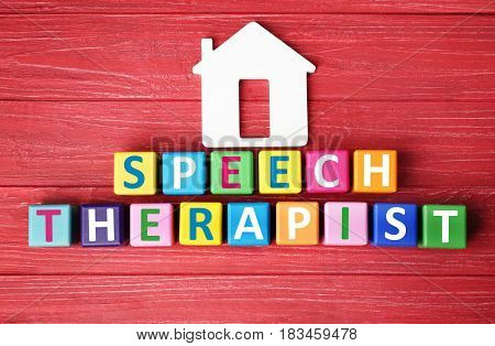 Colourful cubes with text SPEECH THERAPIST on red wooden background