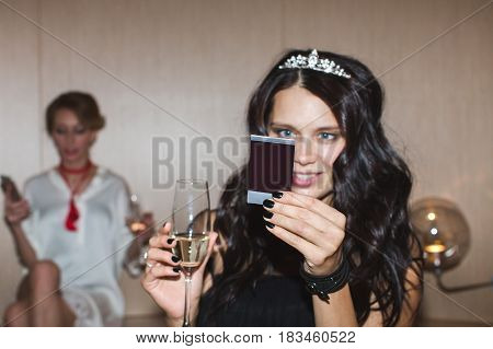 Horizontal indoors shot of a pretty woman with glass of champagne looking at the instant shot.