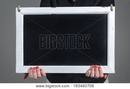 Hands holding empty chalkboard with a lot of free blank copy space for text. Woman showing blank blackboard against dark gray background. Nice template for design, artwork and marketing.