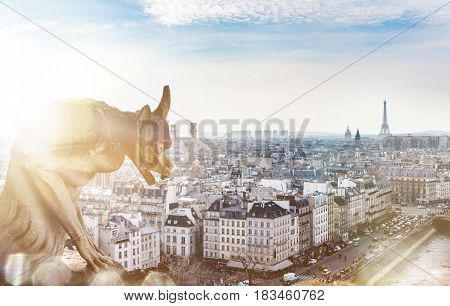 Beautiful view to the whole city of Paris from the top of Notre Dame. An iconic statue of the Cathedrale in the foreground with a ray of sunlight and a flare. The Eiffel Tower visible in the horizon.