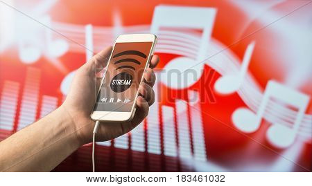Close up of a man holding smartphone in hand and listening to music with mobile app. Red blurred note background. Modern online music streaming concept with free copy space for text.