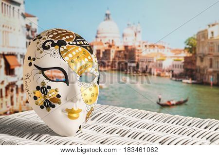Venetian mask with Canal Grande and Santa Maria della Salute church in the background. Traditional souvenir and beautiful view to the city and a gondolier in a gondola. Sunny Venice travel concept