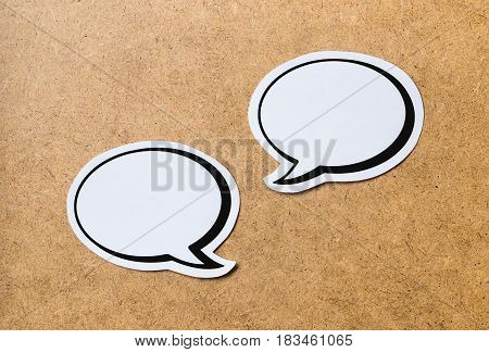 2 blank speech bubbles on a light brown wooden cork board background. Chat bubble cut from paper and cardboard. Discussion, chat and commenting concept with a lot of free empty copy space for text.