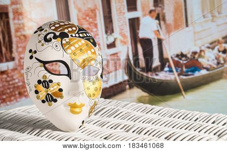 Close up to a golden Venetian mask souvenir. A gondolier row a gondola full of tourists in the blurred background on a beautiful sunny summer day in a canal. Venice holiday and leisure concept.