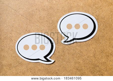 2 speech bubbles on a light brown wooden cork board background. Chat bubble and icon cut from paper and cardboard. Discussion, chat and commenting concept.