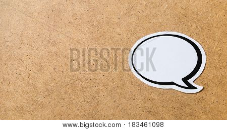 Wooden cork board background texture with a blank speech bubble in the right side. Chat bubble cut from paper and cardboard. Banner style communication, chat and social media concept with copy space.