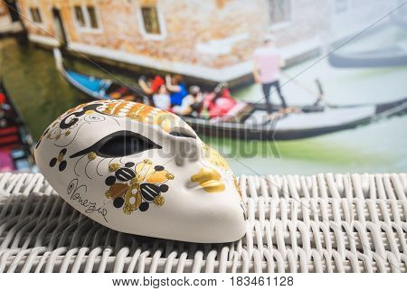 Authentic mask from Venice with a gondolier and tourists in gondola in the background. Golden souvenir and traditional Venetian boat in the world famous canal. Sunny summer travelling in Italy.
