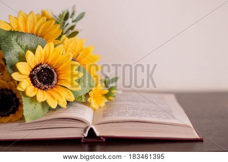 Opened book with yellow flowers on a wood table.
