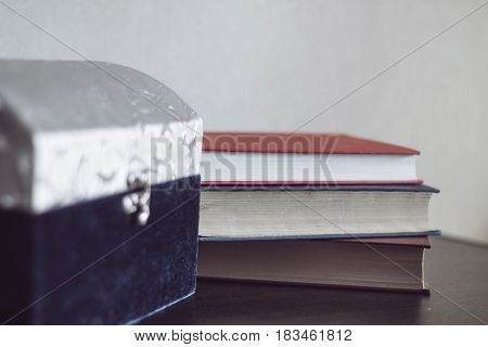 Big casket and three books on a wood table.