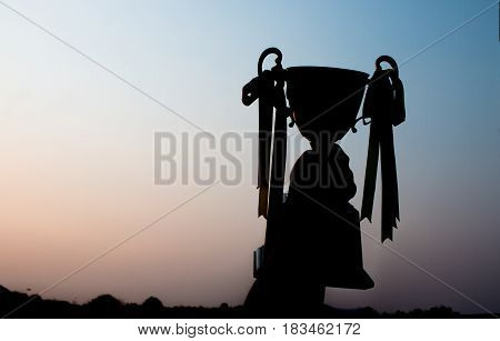 winner and champion concept Silhouette of Hand holding championship trophy against blue sky