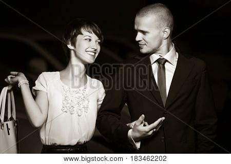 Happy young couple in love. Man and woman walking in night city street. Stylish fashion model outdoor