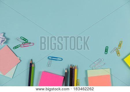 Color pencils, sticky notes, and paper pins on light blue background
