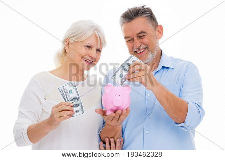 Senior couple holding money and piggy bank