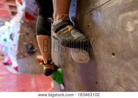 fitness, extreme sport, bouldering, people and healthy lifestyle concept - feet of young woman exercising at indoor climbing gym