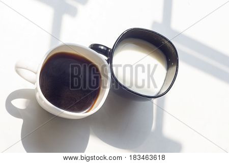 black cup of milk and white cup of coffee on a natural white background top view