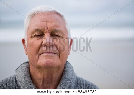 Senior man with eyes closed standing at the beach