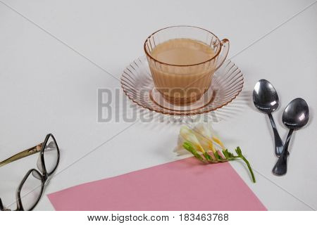Cup of tea, spoons, blank page, spectacles, paper balls and flower on white background