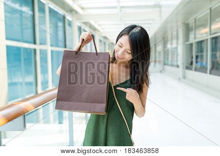 Woman finger pointing to the shopping bag