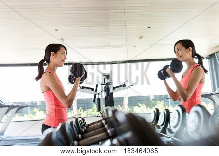 Young sport Woman practices weight lifting of the dumbbell in gym