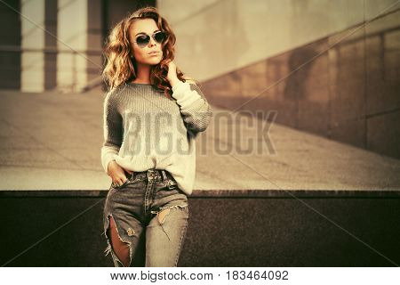 Happy young woman in sunglasses in city street. Stylish fashion model in pullover and ripped jeans outdoor