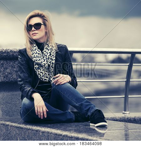 Happy young woman in leather jacket in city street. Stylish fashion model in sunglasses outdoor