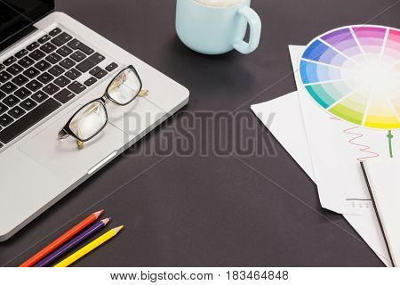Laptop, spectacles, color pencils, coffee cup and color scheme chart on grey background