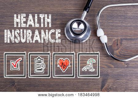 Health Insurance. Stethoscope on wooden desk background