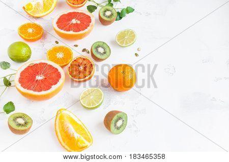 Fruit background. Colorful fresh fruit on white table. Orange tangerine lime kiwi grapefruit