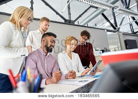 business, teamwork and people concept - international creative team with papers and tablet pc computers at office