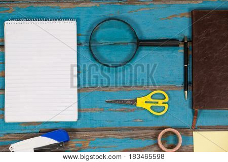 Notepad, magnifying glass, scissor, stapler, pen sellotape and diary on wooden plank