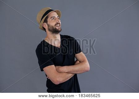 Happy man in black t-shirt and fedora hat standing against grey background
