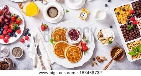 Healthy breakfast for two with coffee, pancakes, fresh berries, quick cereals and orange juice on light gray background, top view.