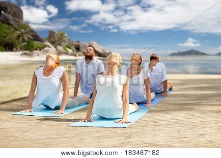 fitness, sport, yoga and healthy lifestyle concept - group of people making cobra pose over tropical beach background