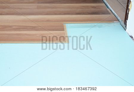 Laminate Wood Flooring. Contractor installing wooden laminate flooring with insulation and soundproofing sheets.