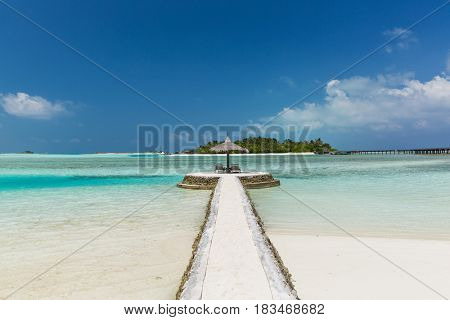 travel, tourism, vacation and summer holidays concept - road to patio or terrace with palapa and sunbeds on maldives beach